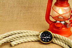 Old burning oil lamp,  compass,  and rope on burlap Royalty Free Stock Photography