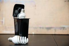 Old burnt fluorescent energy saving lamps. Hazardous and toxic electronic waste stock photos