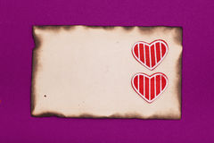 Old burnt paper and two hearts Royalty Free Stock Photo