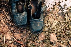 Old shoes on the grass. Old burnt shoes on the burnt grass Stock Images
