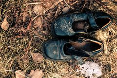 Old shoes on the grass. Old burnt shoes on the burnt grass Royalty Free Stock Photos