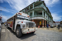 Old bus in Colon Panama. June 9, 2016 Colon, Panama: an old bus rolls in front of a run-down colonial building in the port town royalty free stock photos