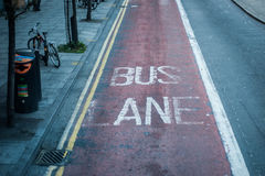 Old bus lane markings on tarmac in London.  Royalty Free Stock Images