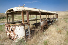 Old bus on the meadow. In background small route. Armenia Royalty Free Stock Photography