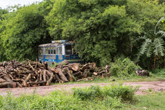 Old bus in the middle of the wood. With old logs nearby image Stock Image