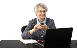 Old business lady calling by phone during skype conv Stock Photography