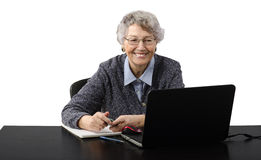 Old business lady laughing during skype conversation Royalty Free Stock Photos