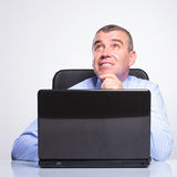 Old business man daydreaming at laptop Stock Image