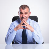 Old business man at desk with hands together Royalty Free Stock Photography