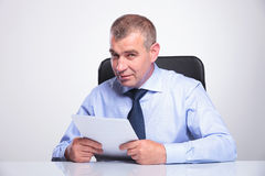 Old business man at desk holds papers Royalty Free Stock Images