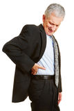 Old business man having back pain. And holding hand to his aching back Royalty Free Stock Photography