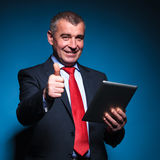 Old business man holding a tablet and making ok Royalty Free Stock Photography