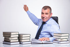 Old business man presents with chalk. Senior bussines man at the desk with many books showing something in the back with some chalk while looking at the camera stock photos