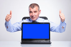 Old business man shows laptop and thumbs up Royalty Free Stock Images