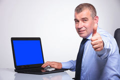 Old business man shows ok from laptop Royalty Free Stock Photography