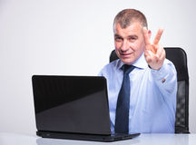 Old business man shows victory behind laptop Royalty Free Stock Image