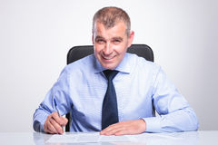 Old business man signs contracts at desk Stock Photos