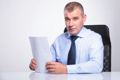 Old business man sits at desk with documents