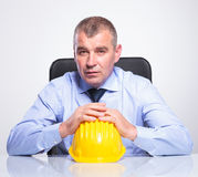 Old business man sits with hands on helmet Stock Image