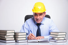 Old business man writes at desk full of books Stock Photo