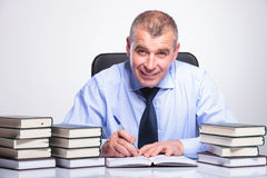 Old business man writes at desk full of books Stock Photography