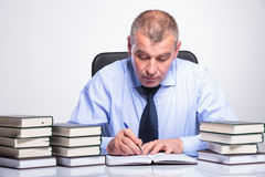 Old business man writes at his desk Stock Photo