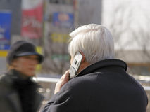 Old businessman. Old grey-haired businessman using mobile phone in a crowded city street Royalty Free Stock Images
