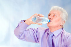 Old businessman drinks water Stock Images