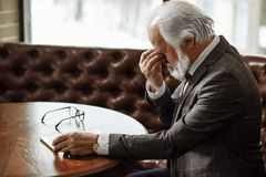 Old businessman has problems with eyes. Senior businessman is blaming himself for what has happened royalty free stock photos