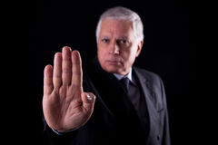 Old businessman  with his hand raised in signal to Stock Photography