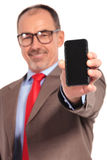 Old businessman showing you the blank screen of his smartphone. Happy old businessman showing you the blank screen of his smartphone on white background Royalty Free Stock Photo