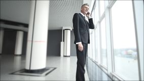 The old businessman speaks on the phone near the panoramic windows. Man talking on a cell phone with a serious look of stock video footage