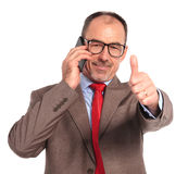 Old businessman talking on the phone makes the ok sign Royalty Free Stock Photo
