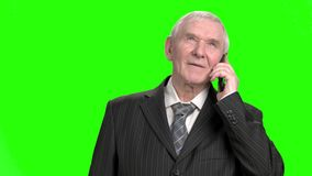 Old businessman talking on phone. Portrait of senior businessman in suit talking on phone, green hroma screen background stock footage