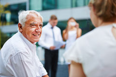 Old businessman talking to business team. During negotiations outdoors Stock Photography