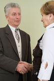 Old businessman thanked his worker. In the office stock image