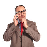 Old businessman thinking while talking on the phone Stock Photo