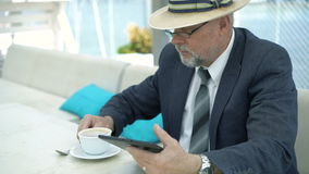 Old businessman using tablet and drinking coffee in cafe. 4K stock video