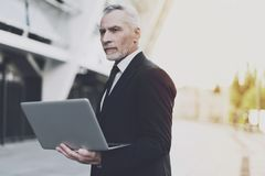 Old businessman working on laptop on the street. Old businessman in a black suit working on laptop. He withdrew his gaze from the screen and pondered Stock Photo