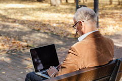 Old businessmen working at laptop outside on a bench Royalty Free Stock Photo