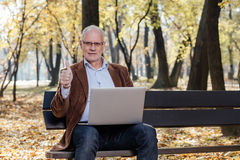 Old businessmen working at laptop outside on a bench Stock Photo