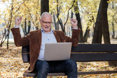 Old businessmen working at laptop outside on a bench Royalty Free Stock Images