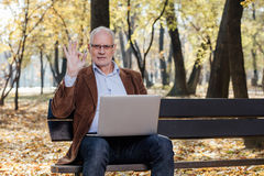Old businessmen working at laptop outside on a bench Royalty Free Stock Photography