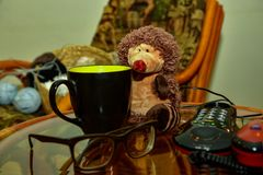 An old button phone next to the glasses, a big black cup and a toy hedgehog stock images