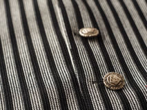 Old buttons on a black man`s vest background with dark stripes, close up Royalty Free Stock Photo