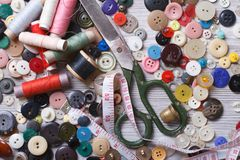 Old buttons, scissors, thimble, thread on a wooden background Stock Photography
