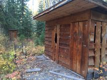 Old Cabin. Old Abandoned Cabin in the Woods with Outhouse Stock Images