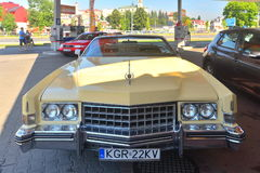 Old Cadillac convertible parked. An ancient American Cadillac convertible car in Gorlice in southern Poland. Market in the background Stock Photos