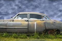 Old Cadillac, Rusty Vintage Car. Fine art photography of an old vintage, retro Cadillac rusty car. The vehicle quietly rests and rusts in a field. Makes a great Royalty Free Stock Photo