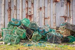 Old cage for lobster and bay with boats in Scotland Royalty Free Stock Photo